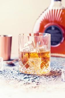 Glas scotch whisky mit eiswürfeln, flaschen- und kupferriegelzubehör