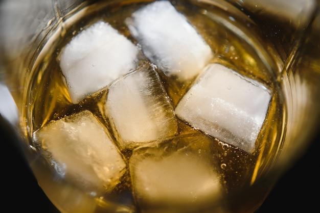 Glas scotch whisky und eis auf schwarz
