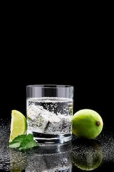 Glas soda oder coctail mit stahlkühlwürfeln auf glas auf dunkler oberfläche