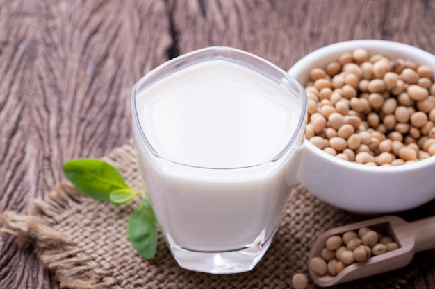 Glas sojabohnenmilch und sojabohnenkorn auf holztisch.
