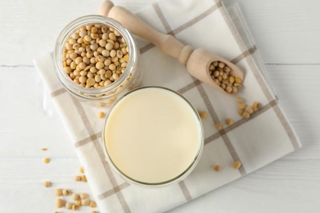 Glas sojamilch, sojabohnensamen, serviette auf weiß, holz, platz für text. draufsicht