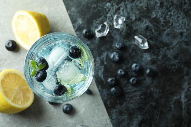 Glas sommercocktail und zutaten auf zweifarbigem hintergrund