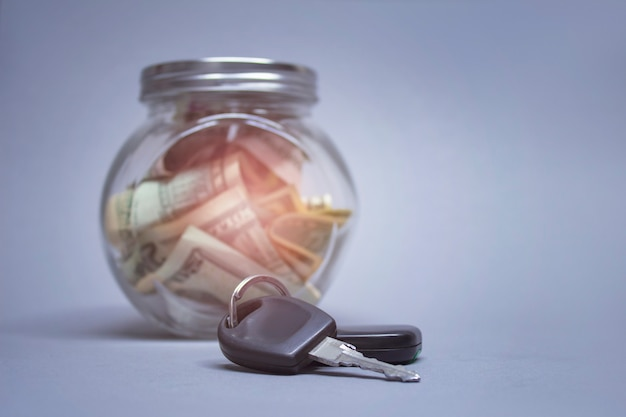 Glas sparschwein mit dollars und autoschlüsseln an einer hellen wand mit glänzendem effekt. geld beiseite gelegt, um ein auto zu kaufen.