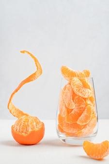 Glas süßer saftiger mandarinensegmente und ganzer orangen-clementine mit schwebender, abgezogener haut