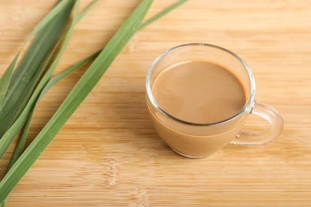 Glas tasse heißen ingwertee mit ingwer-rhizom (wurzel) in scheiben geschnitten isoliert auf holzoberfläche