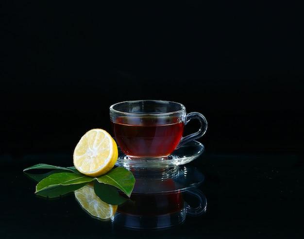 Glas tasse tee auf schwarz.