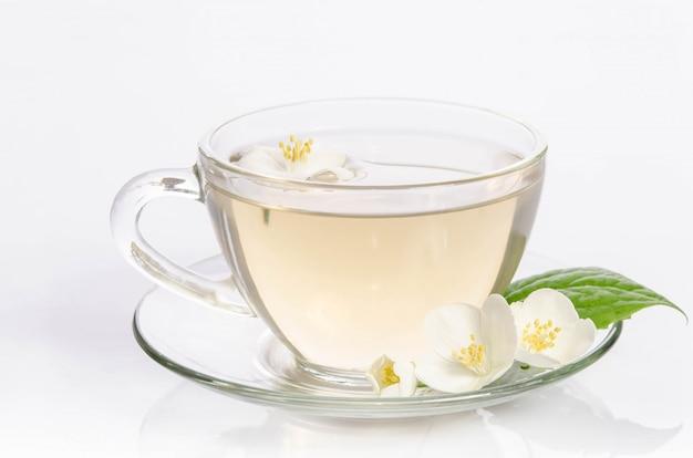 Glas tasse tee mit jasminblüten und blättern