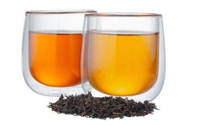 Glas tasse tee mit trockenen teeblättern isoliert
