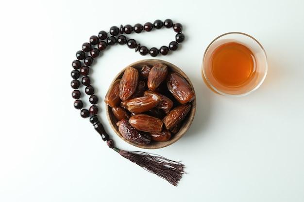 Glas tee, dattelschale und rosenkranz auf weiß