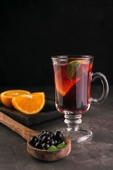 Glas tee mit blaubeeren und orangenscheiben
