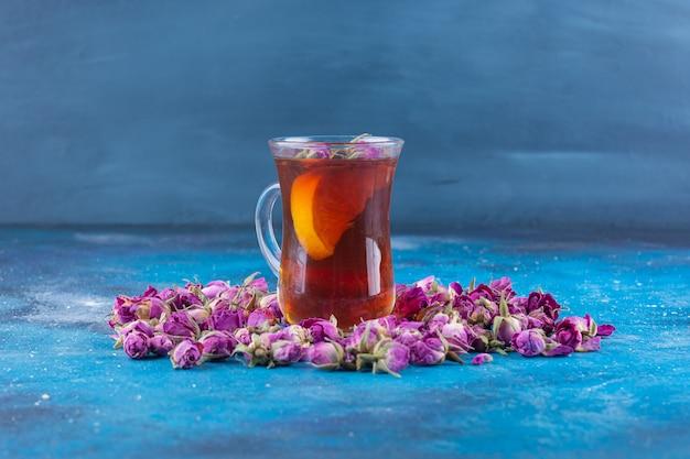 Glas tee mit knospenden rosen auf blauem tisch.