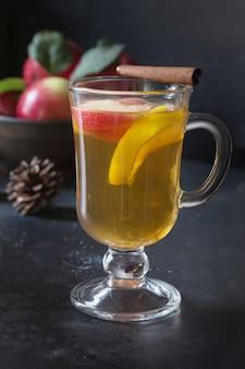 Glas tee mit zitrone, gewürztem, geschnittenem apfel und zimt auf schwarzem brett. herbstliches stillleben.