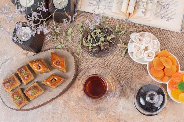 Glas tee, süßigkeiten und traditionelle verschiedene baklavas auf marmortisch.