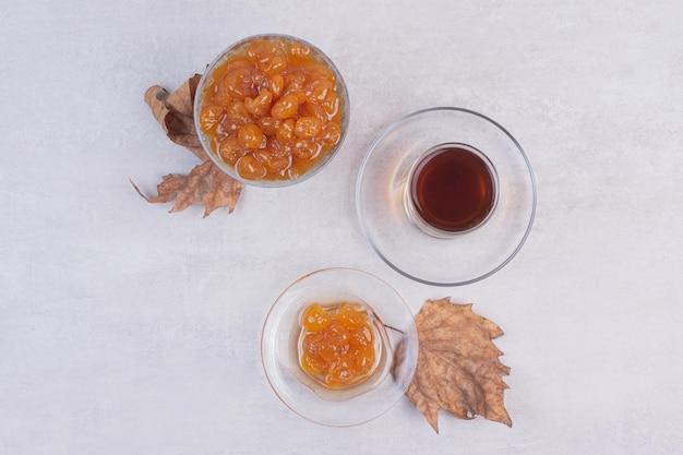 Glas tee und beerenmarmelade auf weißem tisch.