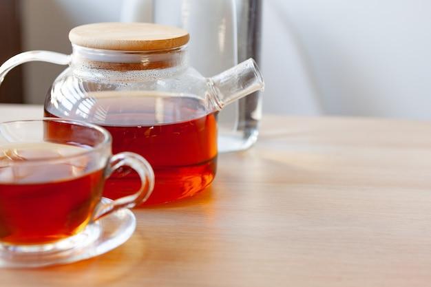 Glas-teekanne mit schwarzem tee auf holztisch