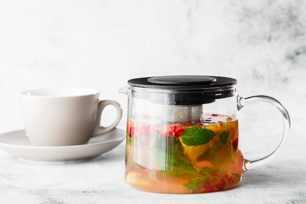 Glas-teekanne von cranberry-, orangen- und minze- oder gelbem tee mit weißer tasse lokalisiert auf hellem marmorhintergrund. draufsicht, speicherplatz kopieren. werbung für cafe-menü. coffeeshop-menü. horizontales foto.