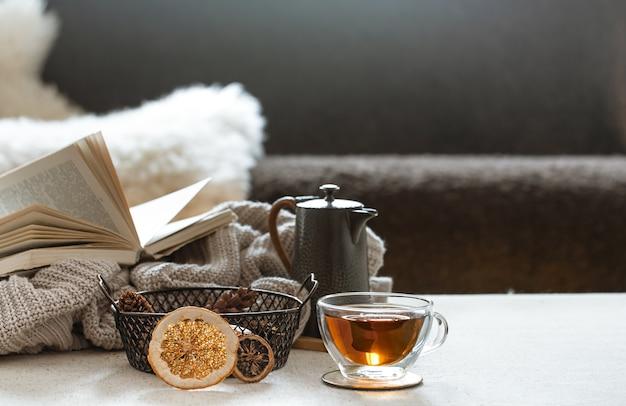 Glas teetasse, teekanne und buch mit gestricktem element auf verschwommenem raum. das konzept von wohnkomfort und wärme.