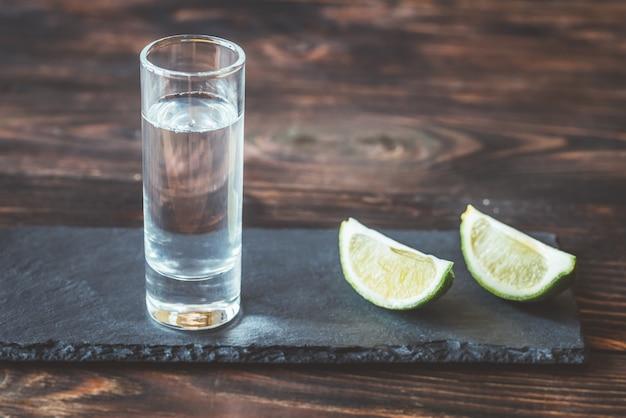 Glas tequila mit limettenschnitzen