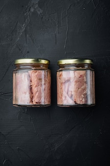 Glas thunfischfilet in olivenöl, auf schwarzem hintergrund, draufsicht mit kopienraum für text