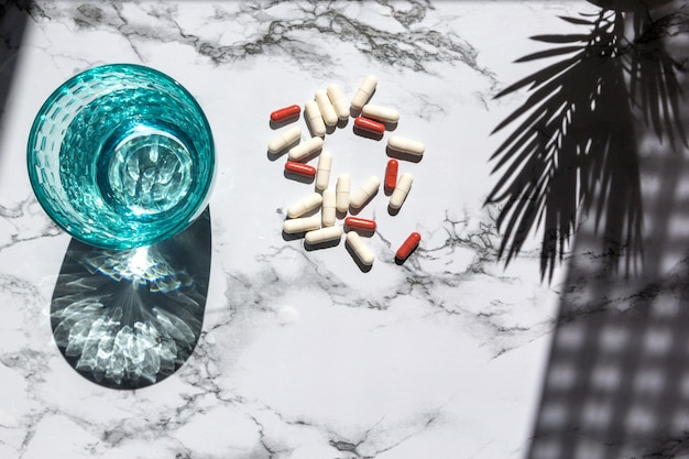 Glas trinkwasser und pillen auf marmorhintergrund mit schatten vom sonnenlicht.