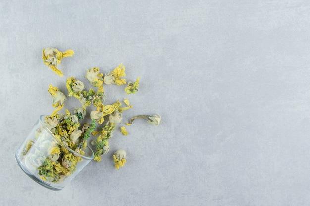 Glas trockene chrysanthemenblumen auf steintisch.