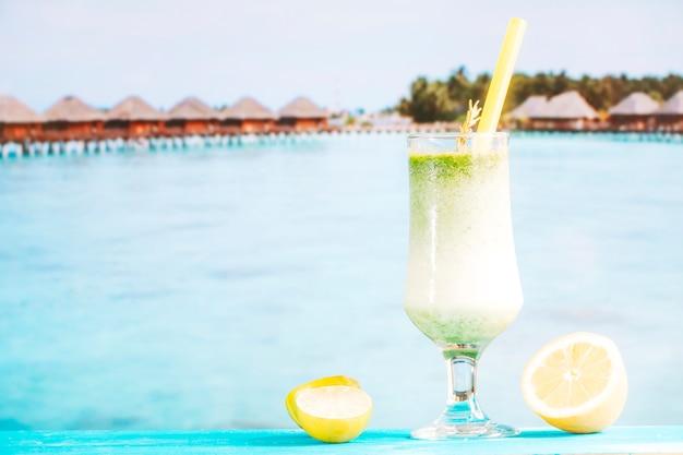 Glas tropischer grüner smoothie und geschnittene zitrusfrucht