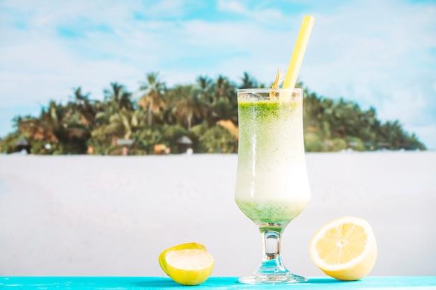 Glas tropischer saurer smoothie und geschnittene zitrusfrucht