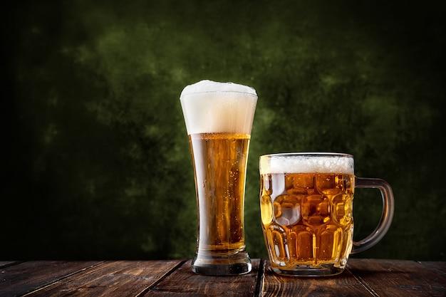 Glas und becher bier auf dunkelgrünem hintergrund