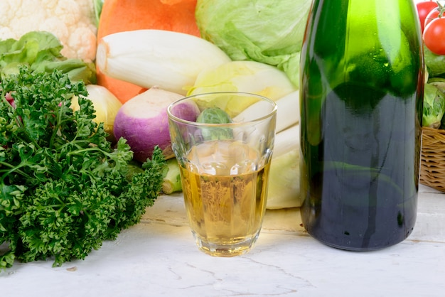 Glas und eine flasche apfelwein mit gemüse