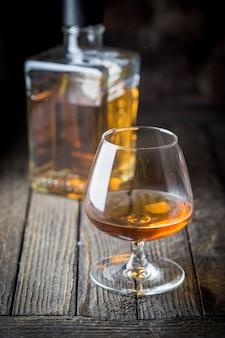Glas und eine flasche brandy oder cognac auf dem holztisch.