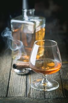 Glas und eine flasche brandy oder cognac und rauchende zigarre auf dem holztisch.
