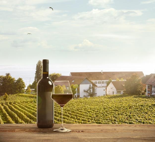 Glas und eine flasche wein auf holzschiene mit ländlicher szene des landes im hintergrund. grüne blätter und ruhiger sommersonnenscheintag. exemplar. alkoholgetränke auf dem hinterhof des großen hauses