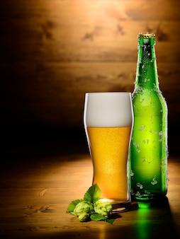 Glas und flasche bier mit hopfen auf holz