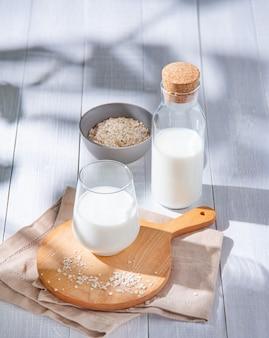 Glas und flasche haferflockenmilch und ein paar verstreute haferflocken auf weißem holz