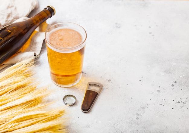 Glas und flasche handwerkliches lagerbier mit rohem weizen und öffner auf steinküchentisch
