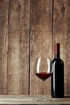 Glas und flasche mit köstlichem rotwein auf tabelle gegen hölzerne wand