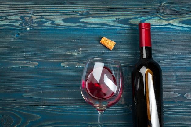 Glas und flasche mit rotwein auf hölzernem hintergrund, draufsicht