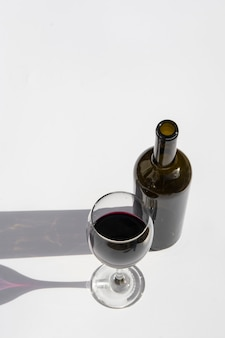 Glas und flasche wein mit den dunklen schatten getrennt auf einem weiß