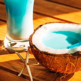 Glas und gebrochene kokosnuss mit hellem blauem getränk