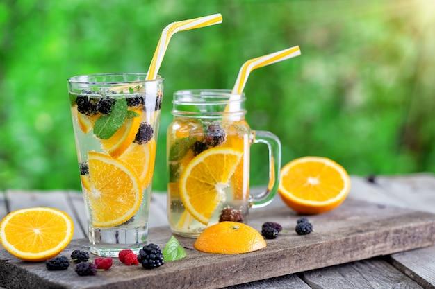 Glas und glas limonadencocktail mit orangenscheiben und beeren
