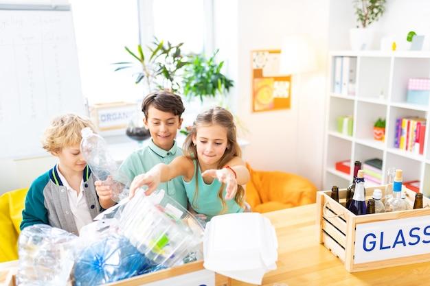 Glas und kunststoff. kinder fühlen sich beim sortieren von glas und plastik im ökologieunterricht wirklich engagiert