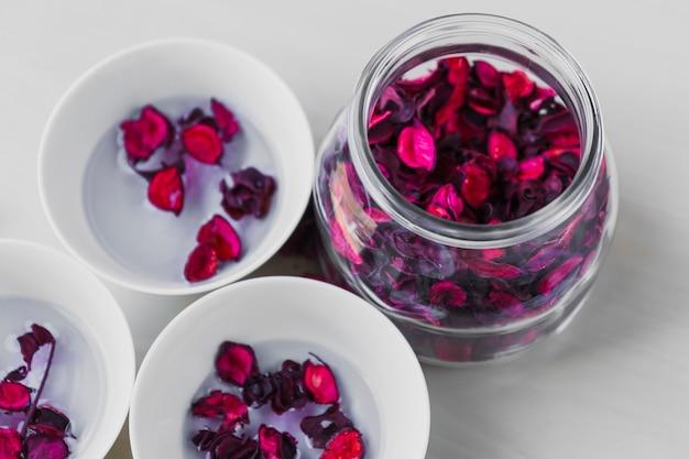 Glas und schüsseln mit blütenblättern