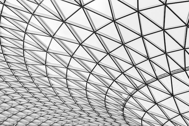 Glas- und stahlgebäude mit dreiecksmusterstruktur. futuristische architektur. architekturstil des neo-futurismus. geometrische kuppelbeschaffenheit des weißen dreiecks.