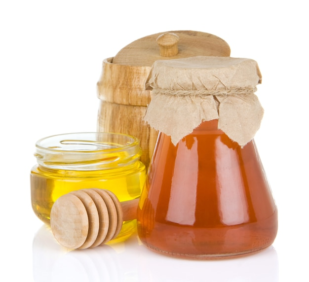 Glas voll honig und stick lokalisiert auf weiß