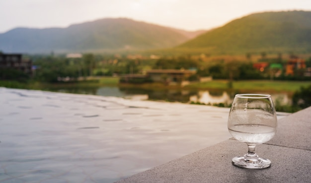 Glas wasser auf boden nahe pool in der modernen villa mit bergblick, seeblick.