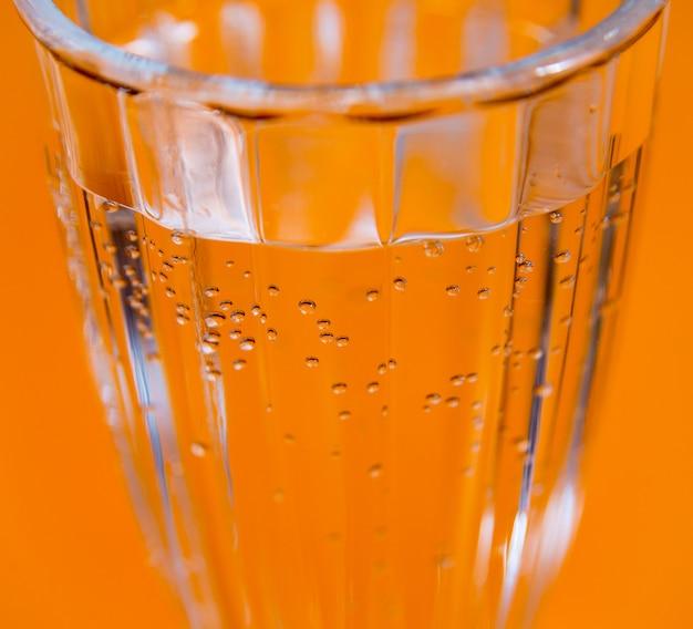 Glas wasser auf dem gelben tisch