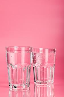 Glas wasser auf einem rosa hintergrund