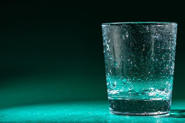 Glas wasser auf einer tabelle auf dunkelheit
