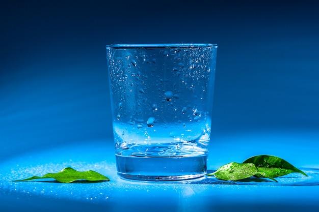 Glas wasser auf einer tabelle auf einer dunkelheit