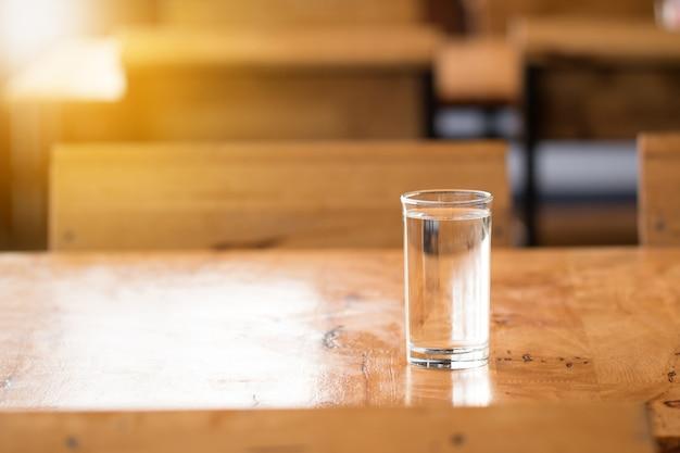 Glas wasser auf holztisch
